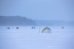 Tents on the snow-covered field near the forest Royalty Free Stock Photography