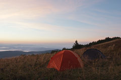Tents at sunrise in mountains Royalty Free Stock Image