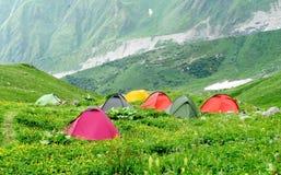 Tentst colorido que stanging no acampamento verde da montanha Fotos de Stock