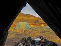 Tentvooruitzicht met paar van de wandelingslaarzen en berg mening bij zonsondergang, Natuurreservaat, hooglanden van IJsland stock foto