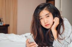 Tenuta abbastanza giovane della donna dell'Asia ed esaminare macchina fotografica sul letto Immagine Stock
