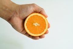 Tenuta arancio organica della fetta sulla mano Immagine Stock