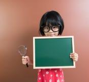 Tenuta asiatica del bambino della scuola una lavagna e una lente d'ingrandimento Fotografia Stock Libera da Diritti