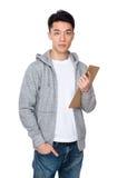 Tenuta asiatica del giovane con il bordo dell'archivio Fotografie Stock