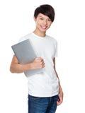 Tenuta asiatica del giovane con il computer portatile Fotografia Stock Libera da Diritti