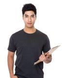 Tenuta asiatica dell'uomo con la lavagna per appunti Immagine Stock