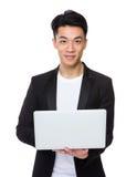Tenuta asiatica dell'uomo d'affari con il computer portatile Fotografia Stock Libera da Diritti