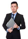 Tenuta asiatica dell'uomo d'affari con il computer portatile Immagini Stock Libere da Diritti