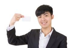 Tenuta asiatica dell'uomo d'affari un biglietto da visita in bianco fotografia stock