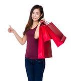 Tenuta asiatica della donna con il sacchetto della spesa ed il pollice su Fotografia Stock Libera da Diritti
