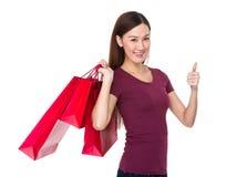 Tenuta asiatica della donna con il sacchetto della spesa ed il pollice su Immagine Stock