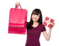 Tenuta asiatica della donna con il sacco di carta e la scatola attuale Immagini Stock