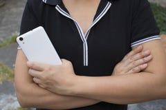 Tenuta asiatica della donna ed usando il lato di manifestazione dello Smart Phone indietro immagini stock