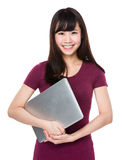 Tenuta asiatica della giovane donna con il computer portatile Immagine Stock