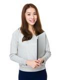 Tenuta asiatica della giovane donna con il computer portatile Fotografia Stock Libera da Diritti