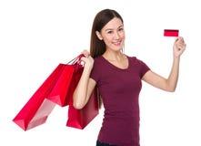 Tenuta asiatica della giovane donna con il sacchetto della spesa e la carta di credito Fotografie Stock Libere da Diritti