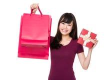 Tenuta asiatica della giovane donna con il sacchetto della spesa e la scatola attuale Fotografia Stock Libera da Diritti