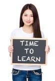 Tenuta asiatica della giovane donna con la lavagna che mostra frase di tempo a Fotografie Stock Libere da Diritti