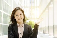 Tenuta asiatica della mano della donna di affari qualcosa Fotografie Stock