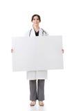 Tenuta asiatica di medico un bordo in bianco Fotografia Stock