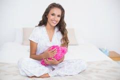 Tenuta castana attraente contenta un cuscino del cuore Fotografie Stock