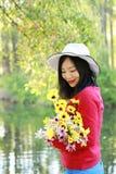 Tenuta che cinese asiatica felice di sorriso della ragazza di bellezza della donna un mazzo di passeggiata del fiore dal lago nel Immagine Stock