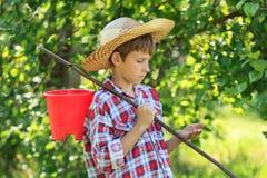 Tenuta d'uso del cappello di paglia del ragazzo qualcosa in braccio Immagine Stock