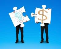 Tenuta dei 2 puzzle con il disegno di simbolo dei soldi e della lampadina Immagine Stock