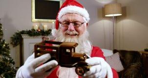 Tenuta del Babbo Natale ed esaminare un'automobile del giocattolo stock footage