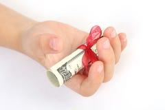 Tenuta del bambino in un regalo della mano delle banconote in dollari dell'americano cento dei soldi con il nastro rosso su fondo Fotografia Stock