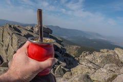Tenuta del compagno tradizionale al picco della montagna Fotografia Stock