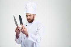 Tenuta del cuoco del cuoco unico e coltelli considerare Fotografie Stock