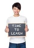 Tenuta del giovane con la lavagna che mostra frase di tempo di imparare Fotografie Stock