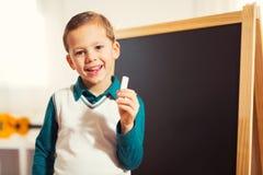 Tenuta del ragazzino con il gesso per la lavagna Fotografia Stock Libera da Diritti