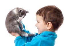 Tenuta del ragazzino nel gattino adorabile delle mani Immagine Stock