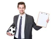 Tenuta del responsabile di calcio con calcio e la lavagna per appunti Immagine Stock Libera da Diritti