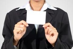 Tenuta dell'Asia della donna di affari ed indicato un biglietto da visita sulle sedere bianche immagini stock