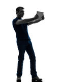 Tenuta dell'uomo che guarda la siluetta digitale della compressa Immagini Stock
