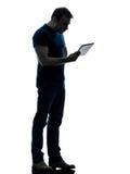 Tenuta dell'uomo che guarda la siluetta digitale della compressa Fotografia Stock Libera da Diritti