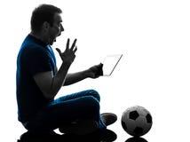 Tenuta dell'uomo che guarda la siluetta digitale della compressa Immagine Stock