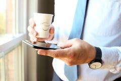 Tenuta dell'uomo d'affari e per mezzo dello Smart Phone mobile Tazza del cofee o del T Fotografie Stock