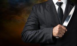 Tenuta dell'uomo d'affari sul coltello immagini stock libere da diritti