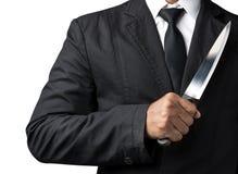 Tenuta dell'uomo d'affari sul coltello immagine stock