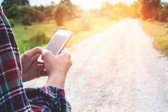 Tenuta dell'uomo del viaggiatore e smartphone usando vintag di concetto di viaggio fotografia stock