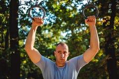 Tenuta dell'uomo sugli anelli di ginnastica Immagini Stock Libere da Diritti