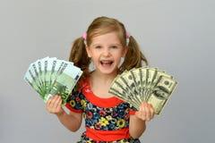 Tenuta della bambina in mani un il pacchetto dei dollari e dell'euro Fotografie Stock Libere da Diritti