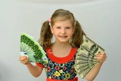 Tenuta della bambina in mani un il pacchetto dei dollari e dell'euro Immagini Stock Libere da Diritti