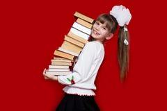 Tenuta della bambina molti libri isolati su rosso Concetto di conoscenza o della scuola Fotografia Stock