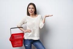 Tenuta della donna che mostra indicare vuoto del cestino della spesa fotografia stock libera da diritti