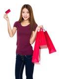 Tenuta della donna con il sacchetto della spesa e la carta di credito Immagine Stock